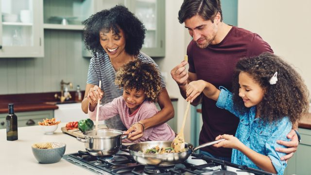 A mother and father cook at the stove in the kitchen with their two young daughters