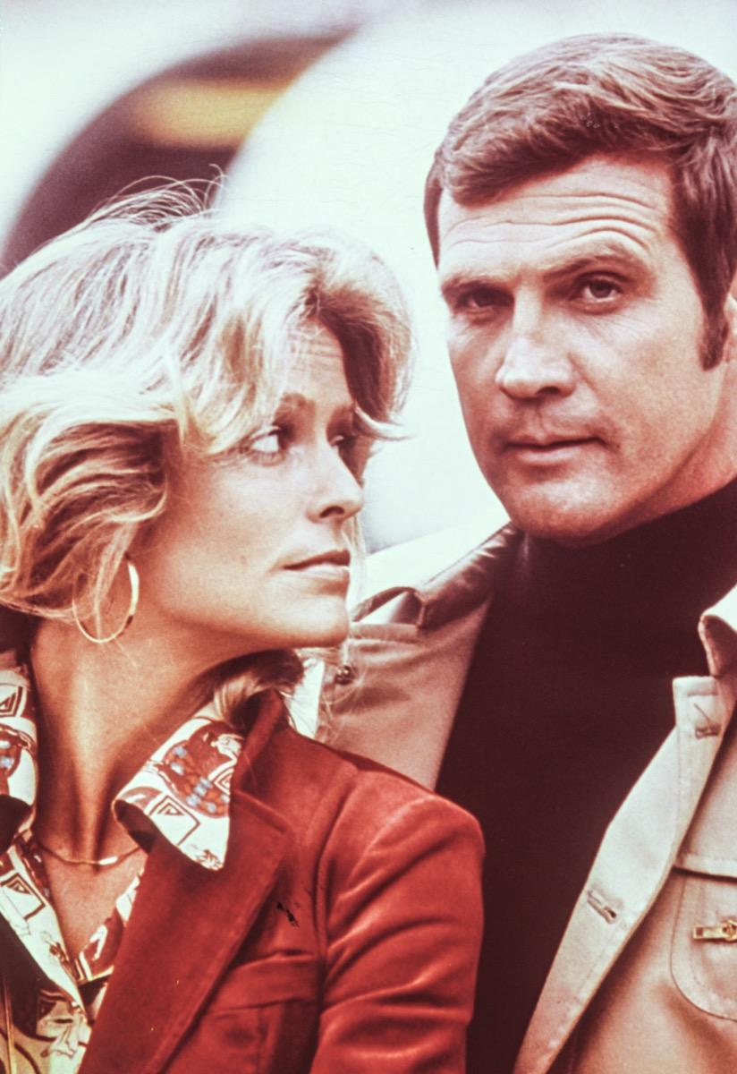 Farrah Fawcett wears a red jacket and Lee Majors wears a beige jacket and black shirt