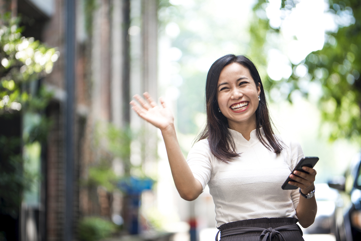 Portrait of a friendly woman on the street waving at someone with a big smile on her face
