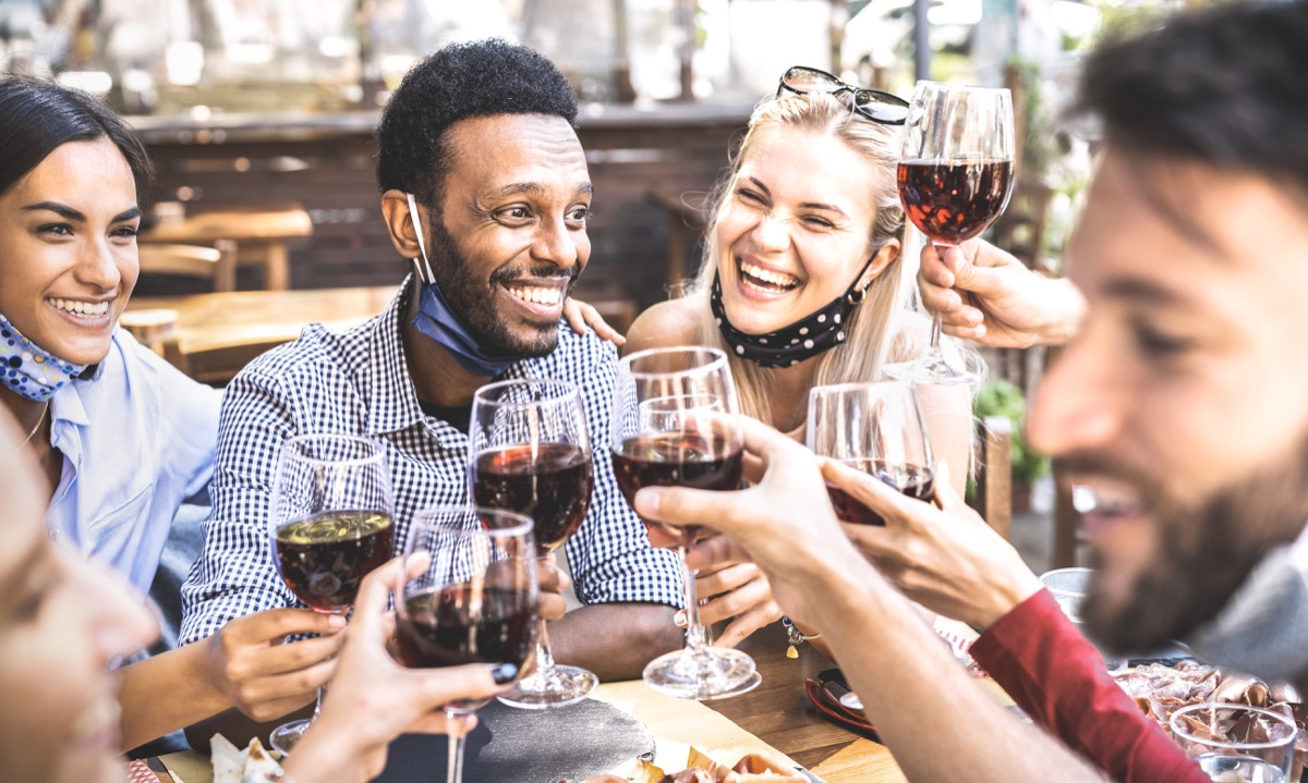 Friends toasting red wine at outdoor restaurant bar with open face mask - New normal lifestyle concept with happy people having fun together on warm filte