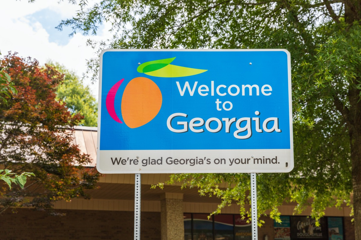 """a blue """"Welcome to Georgia"""" sign in front of trees and a building"""
