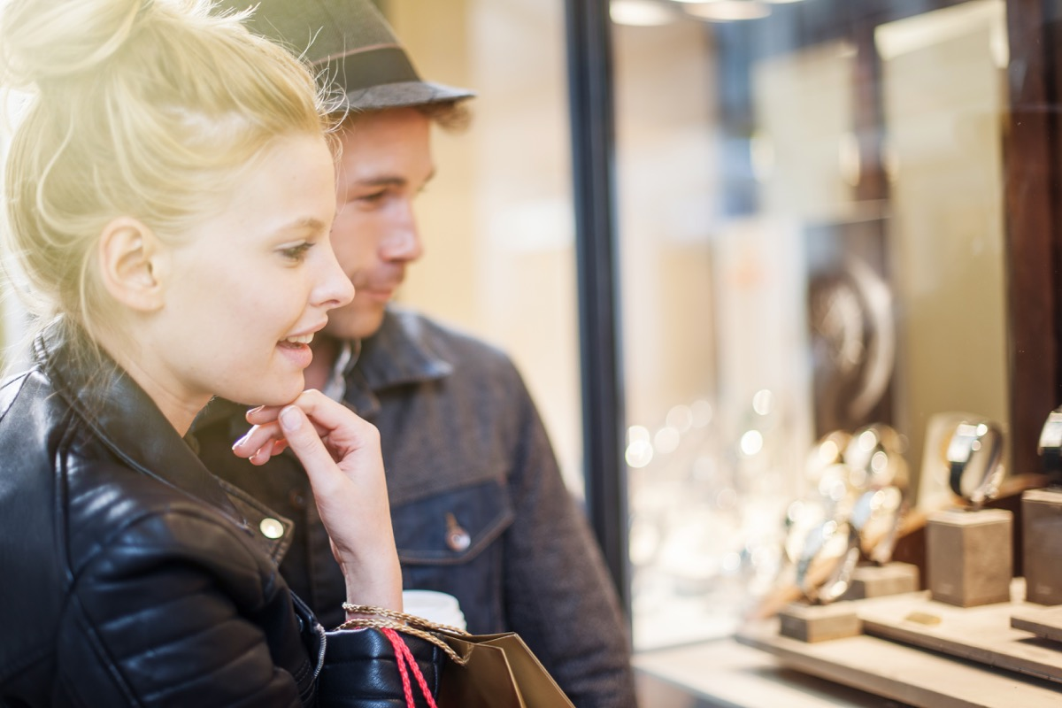 Woman looking at jewelry window hopping he will buy something for her