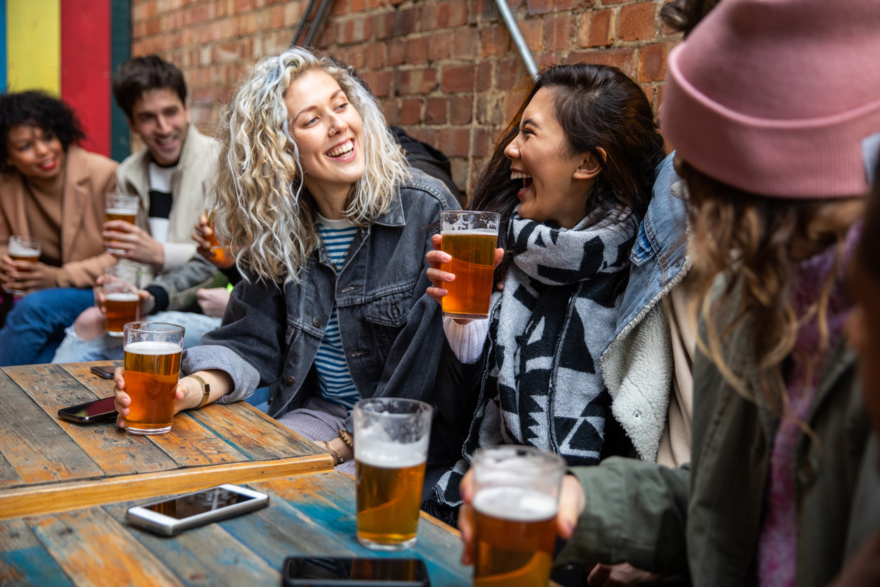 A group of young friends laughing and enjoying beers at a pub while not wearing face masks.