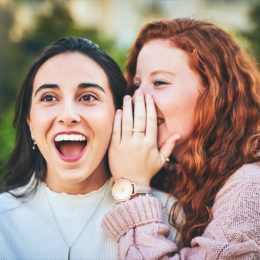 Shot of a woman whispering something into her friend's ear