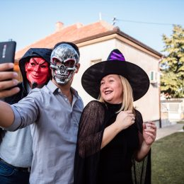 Young man with a skeleton mask taking selfie with his friends in Halloween