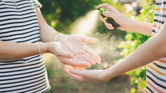 A person sprays a hand sanitizer on their friends outstretched hands to stop the spread of the coronavirus and the flu.