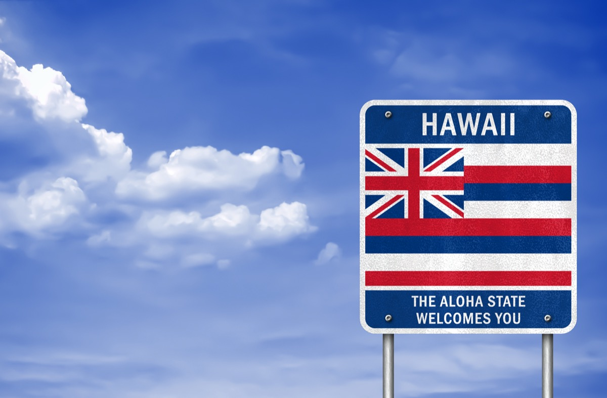 """A blue sign thats """"Hawaii"""" and with the flag on it"""