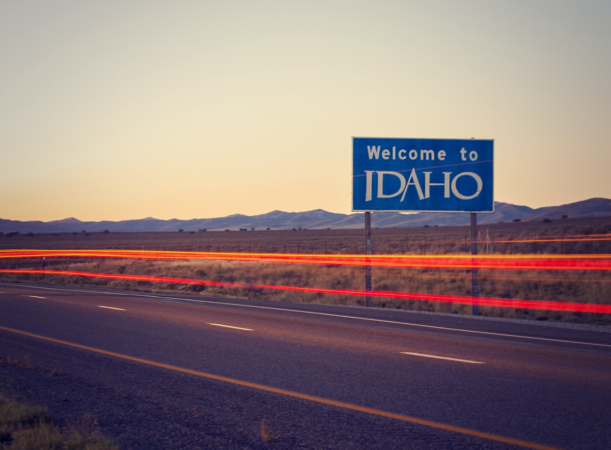 """a blue """"Welcome to Idaho"""" sign off of a highway at dusk"""