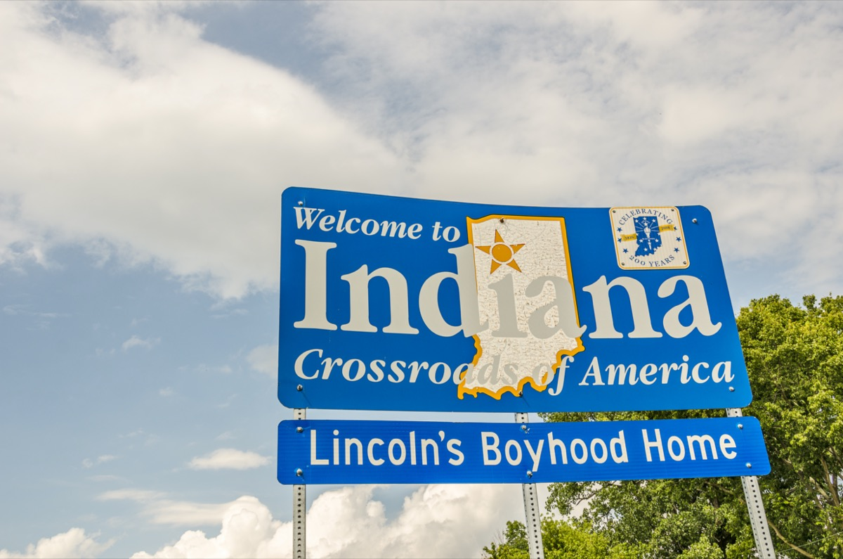 """a blue """"Welcome to Indiana"""" sign in front of green trees"""