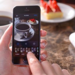 İstanbul, Turkey - January 23, 2015: Woman hands holding an Apple iPhone 5s and taking photos of a dessert and coffee cup with Instagram application. iPhone is a touchscreen smart phone produced by Apple Inc.