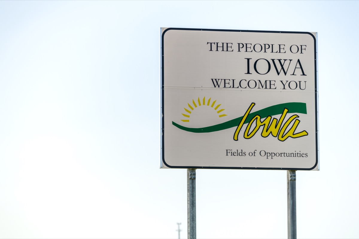 """a white """"The People of Iowa Welcome You"""" sign"""