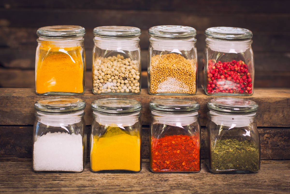 eight small glass jars of spices, in yellow, red, green, and white colors, on natural wood shelves