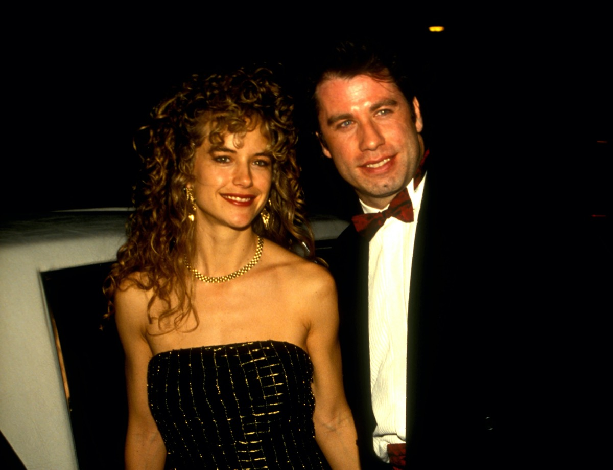 John Travolta wears a black suit and white shirt and Kelly Preston wears a black dress outside of a restaurant in 1991