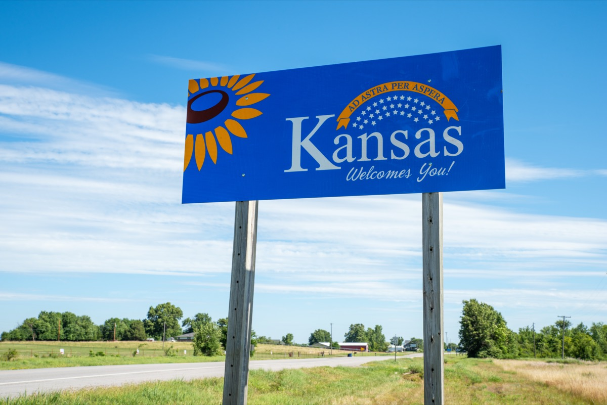 """a blue """"Kansas Welcomes You!"""" sign off of a highway"""