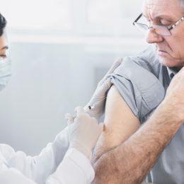 Closeup portrait nurse doing injection to senior man
