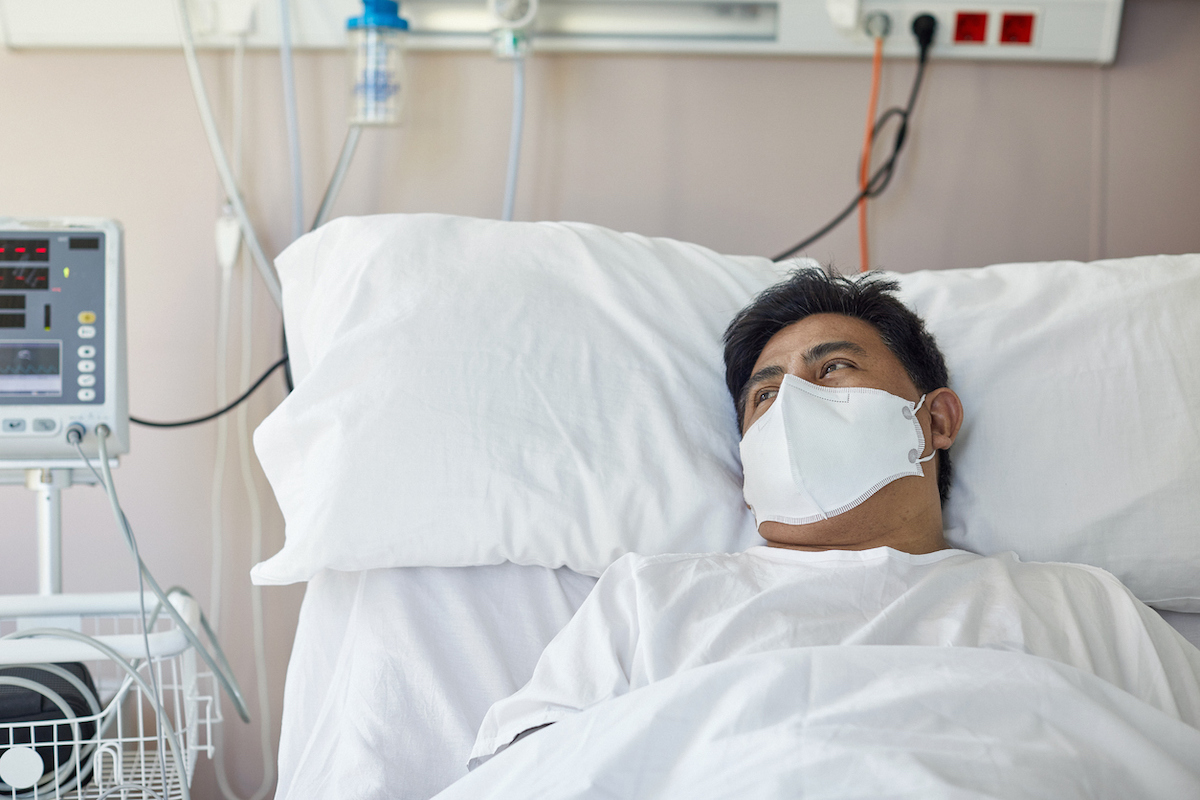 Portrait of male patient in early 40s looking away from camera while lying in hospital bed wearing protective face mask and recovering from coronavirus.