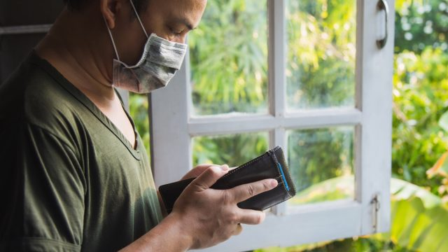 Close up man in green casual shirt wearing a flu mask looking at his wallet, he is standing next a window with green nature blurred background.