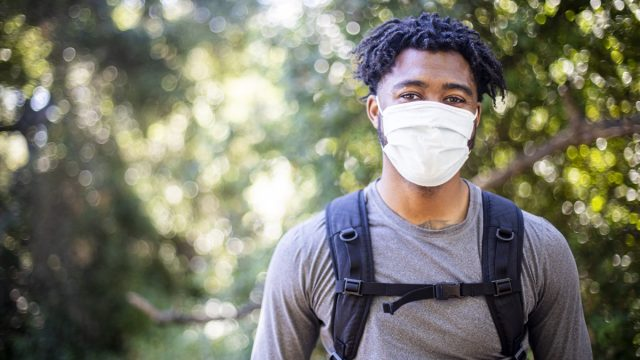A young black man wearing a face mask on a hike