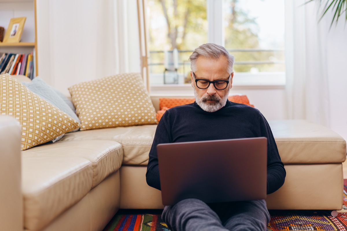 Senior man sitting using a laptop at home relaxing on the floor of the living room leaning against the sofa