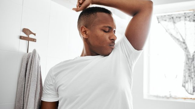 Shot of a young man smelling his underarms while standing in the bathroom