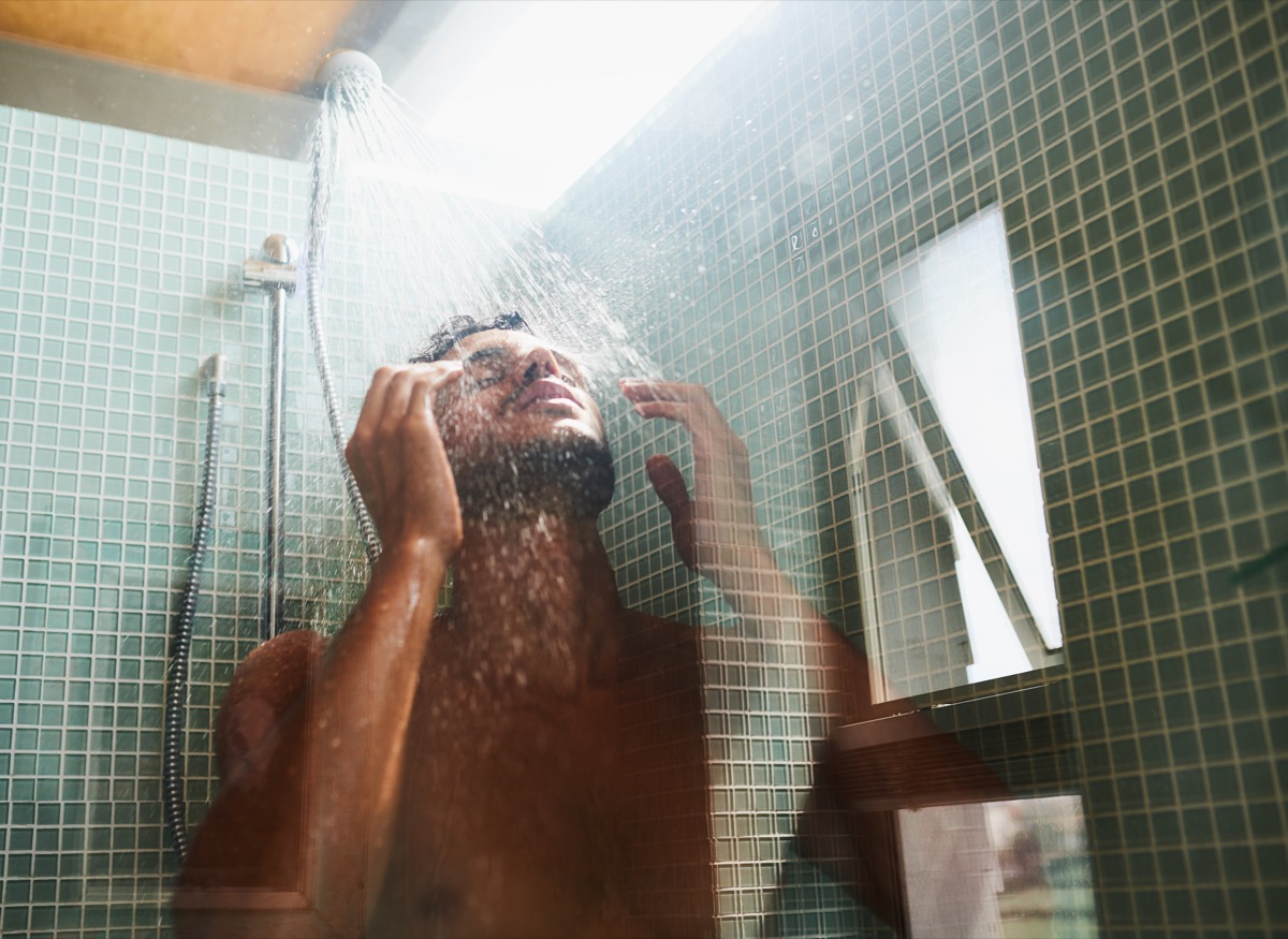 Cropped shot of a man having a refreshing shower at home