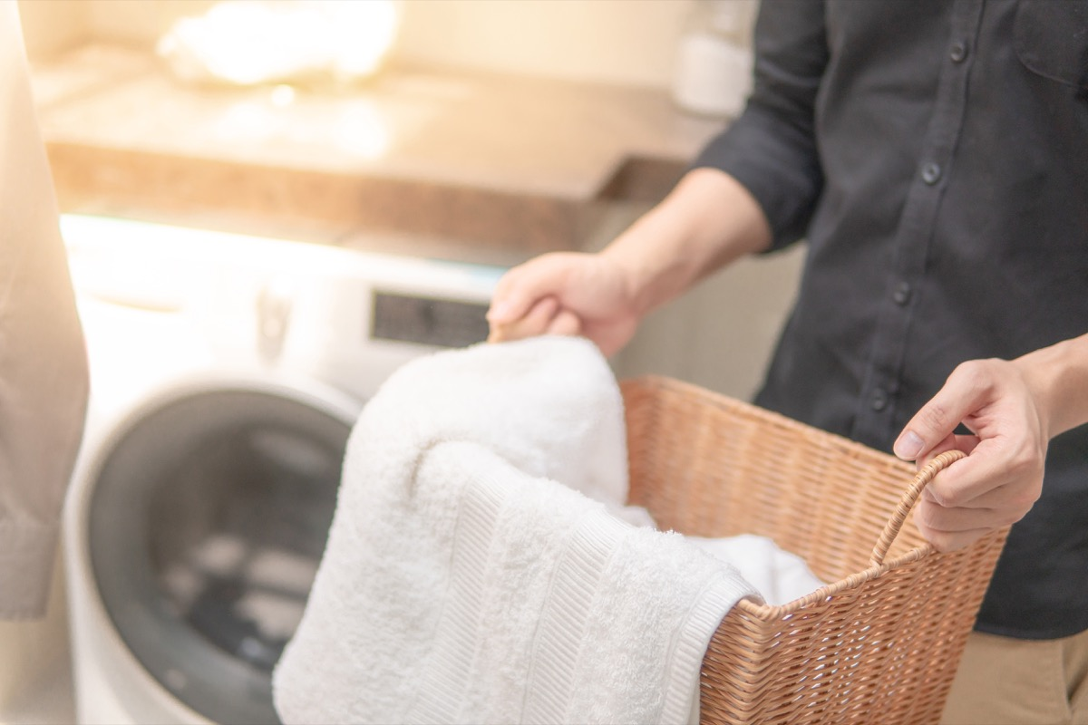 Male hand holding wooden laundry basket with white towel inside near washing machine in laundry room. Home living concept