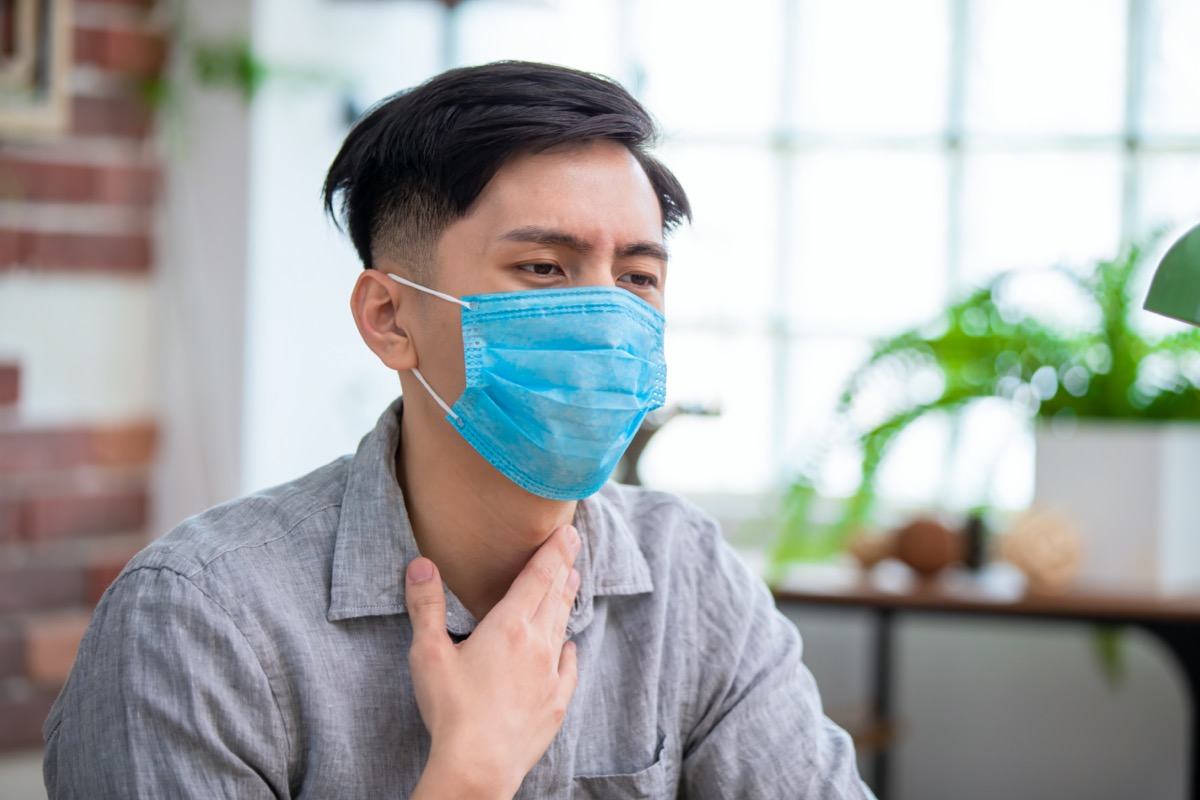man has sore throat and wear face mask at home