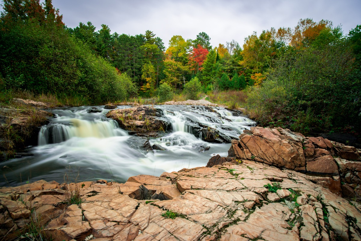 waterfall, green trees, and rocks in Marquette, Michigan