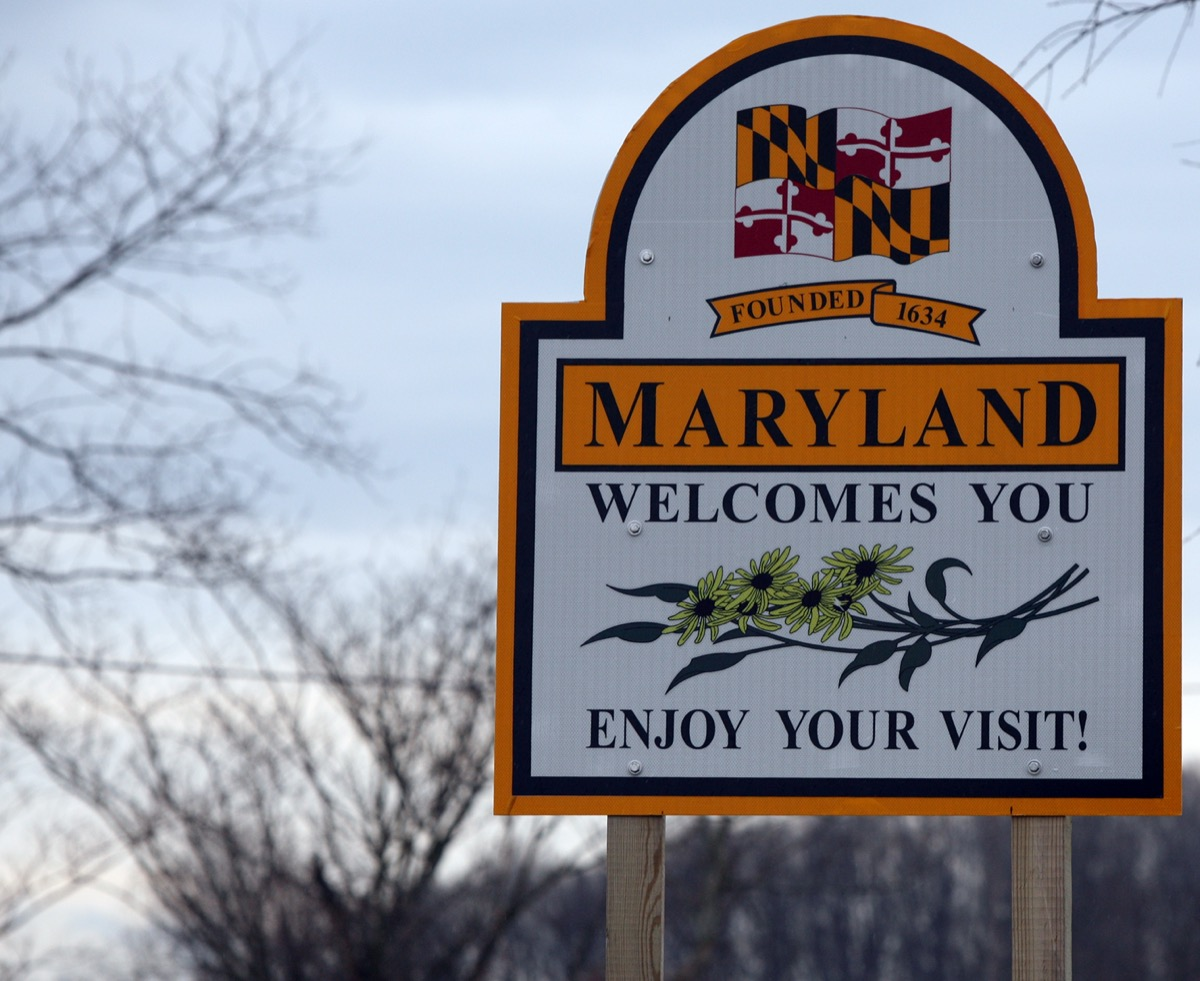 """a """"Maryland Welcomes You"""" sign with a white background and oranger border"""