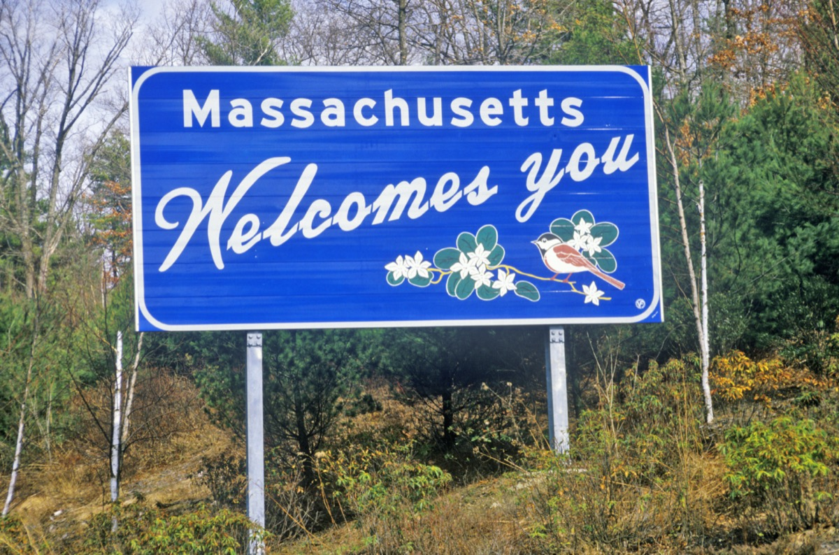 """a blue """"Massachusetts Welcomes You"""" sign in front of green trees"""