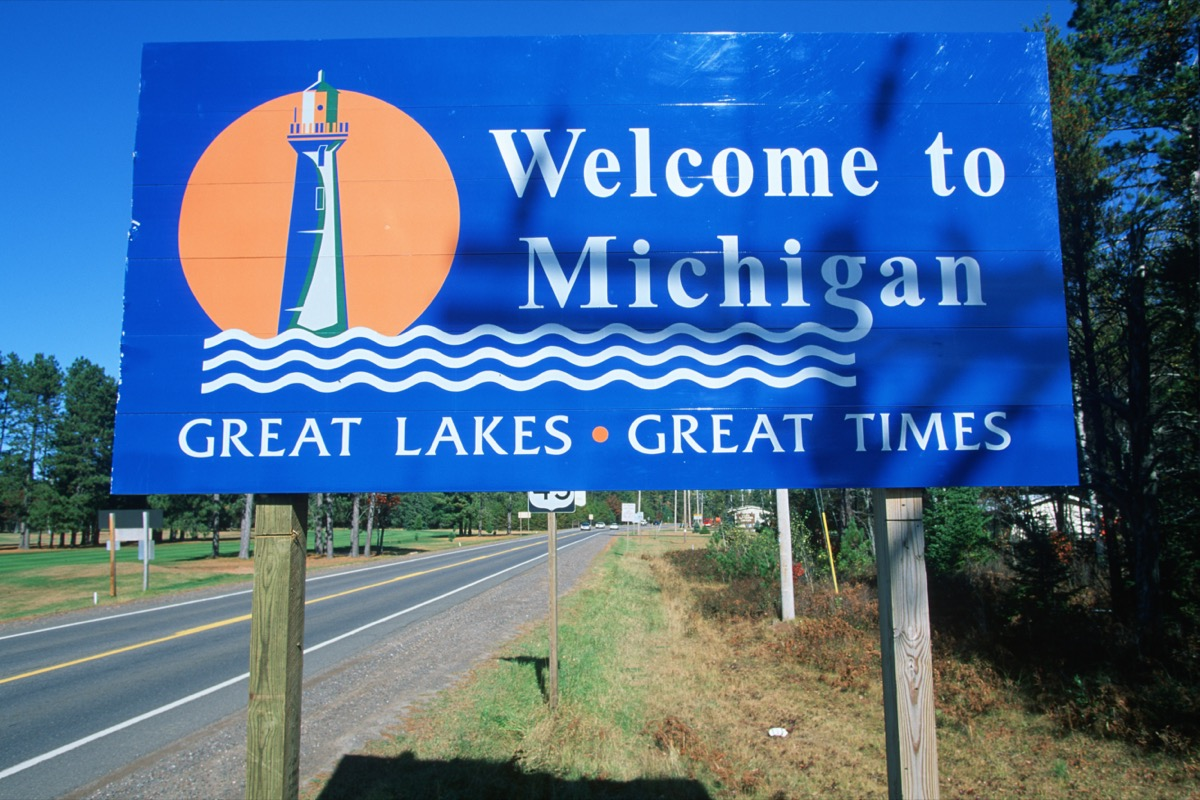 """a blue """"Welcome to Michigan"""" sign off of a highway"""
