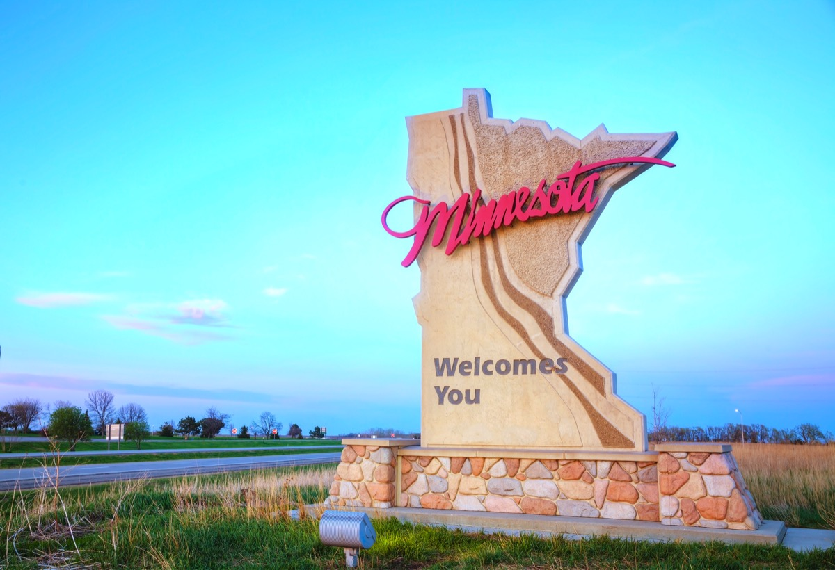 """a beige """"Minnesota Welcomes You"""" sign within grass and off the road"""