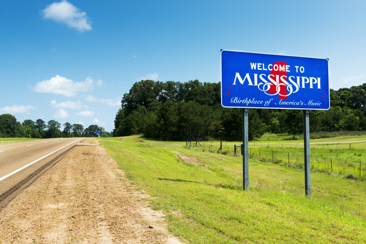 """a blue """"Welcome to Mississippi"""" sign off of a highway and within the grass"""