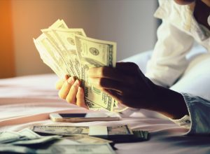 Woman holding a lot of money in bed