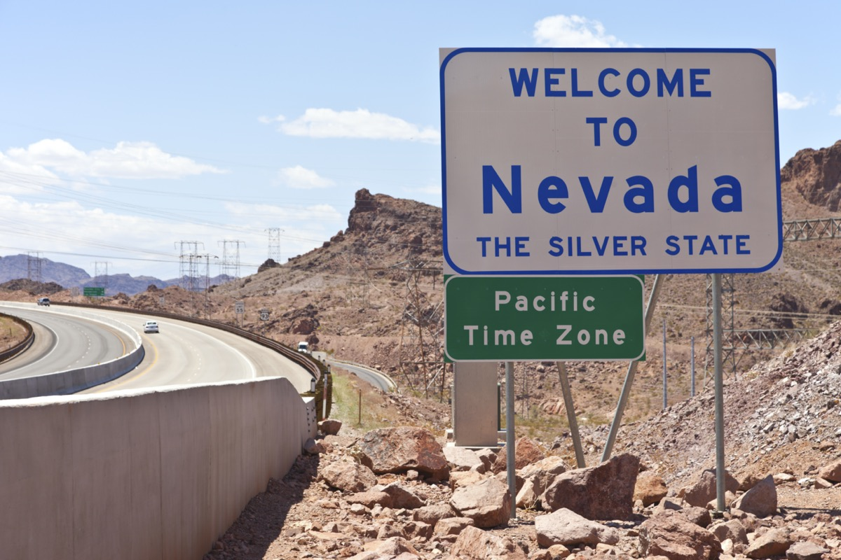 """a white """"Welcome to Nevada"""" sign off of a highway and within dirt and rocks"""