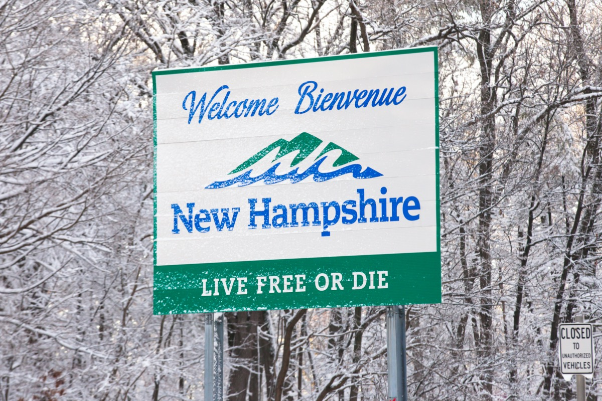 """a white """"New Hampshire"""" sign in front of trees that have snow on them"""