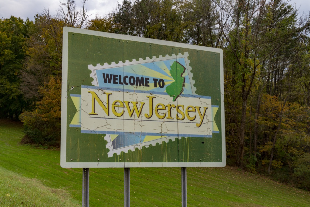 """a green """"Welcome to New Jersey"""" sign in front of green and yellow trees"""