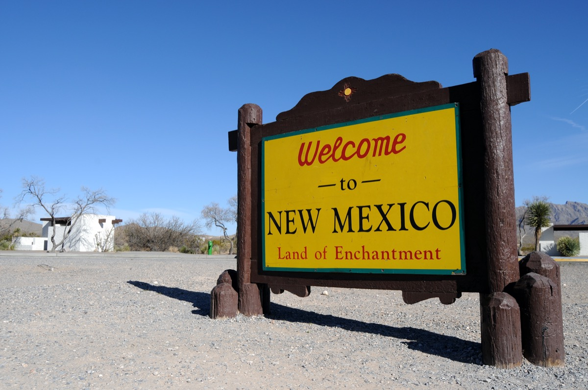 """a """"Welcome to New Mexico"""" sign with a yellow background and wooden border"""