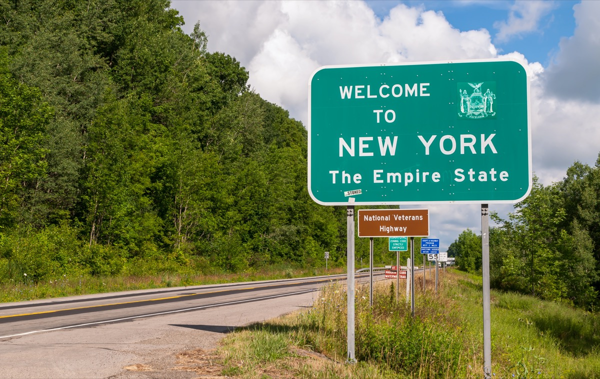 """a green """"Welcome to New York"""" sign off a highway"""