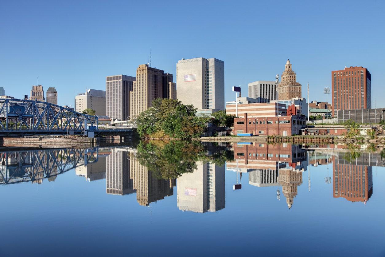 The skyline of Newark, New Jersey as shot from the Passaic River with a rail bridge on the left of the frame