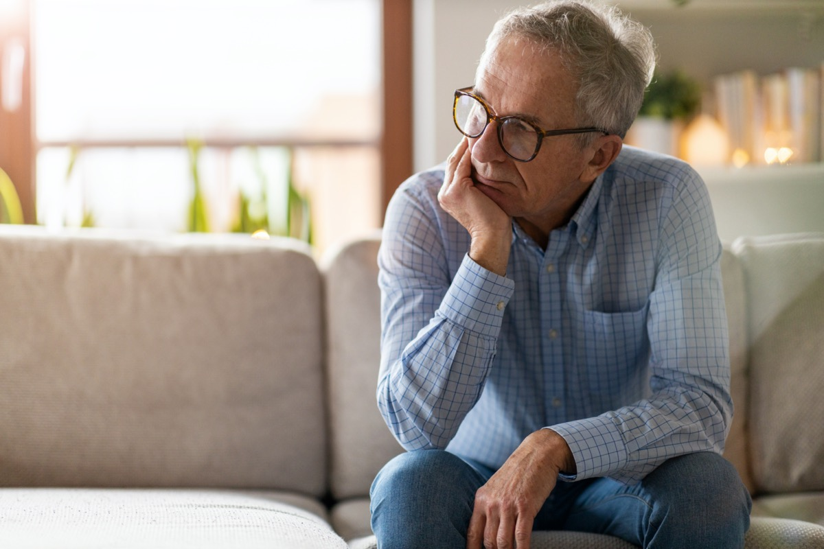 Worried senior man sitting alone in his home