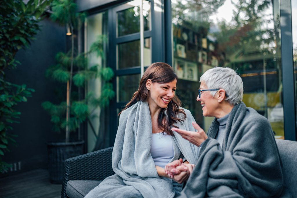 An older woman and younger woman sit on a patio talking to each other