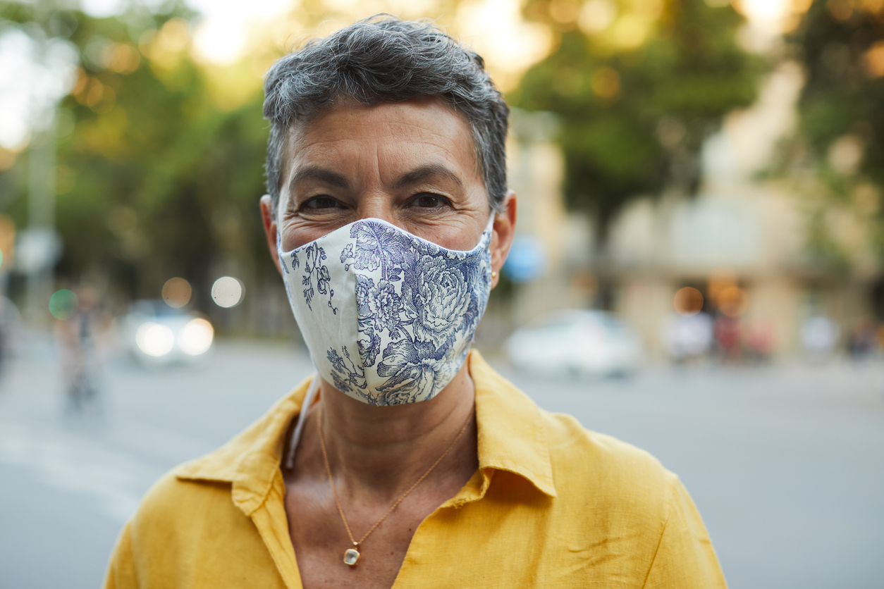A middle-aged woman in a yellow shirt smiles while wearing a cloth face mask