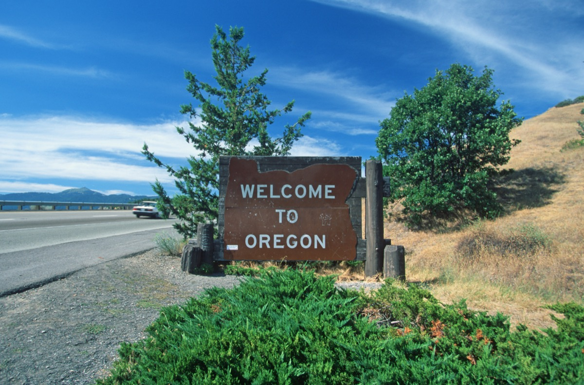 """a wooden """"Welcome to Oregon"""" sign in front of trees and off of a highway"""