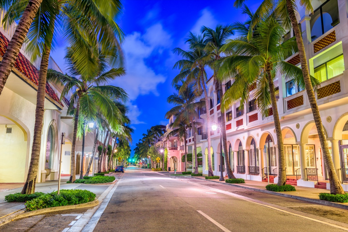 empty street, palm trees, and white buildings in Palm Beach, Florida at night
