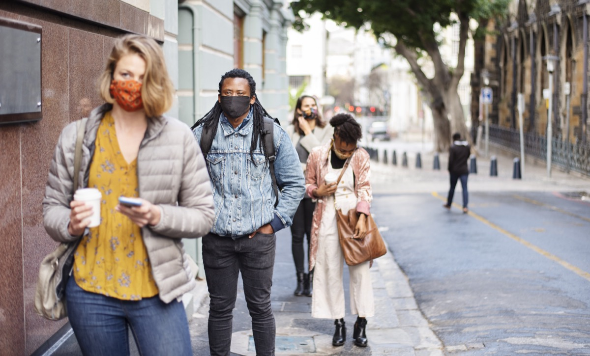 Group of diverse people in face masks social distancing on a city sidewalk