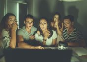 College students watching scary movie on laptop