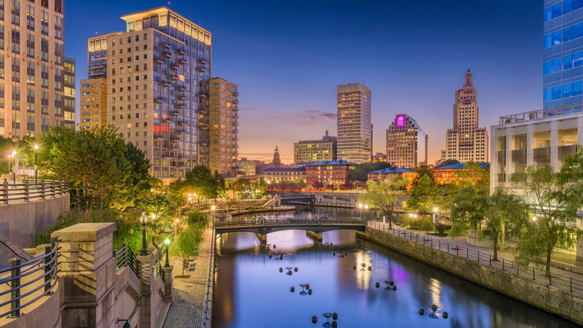 buildings and walking bridge by a lake in Providence, Rhode Island at night