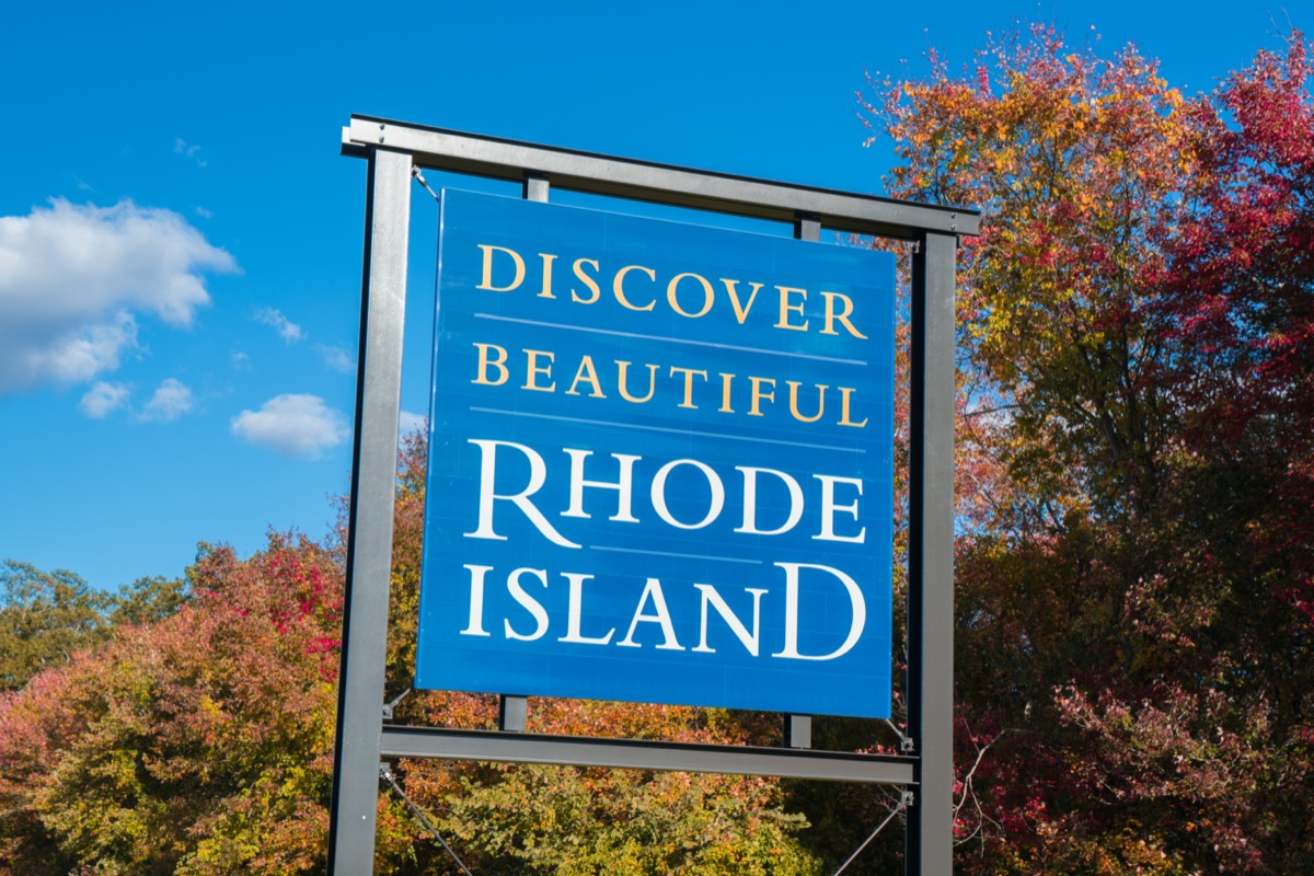 """a blue """"Discover Beautiful Rhode Island"""" sign in front of red and yellow trees"""
