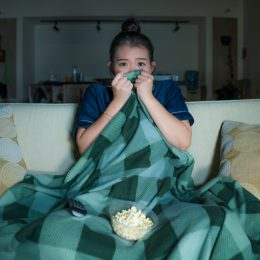 scared young asian woman watching horror movie